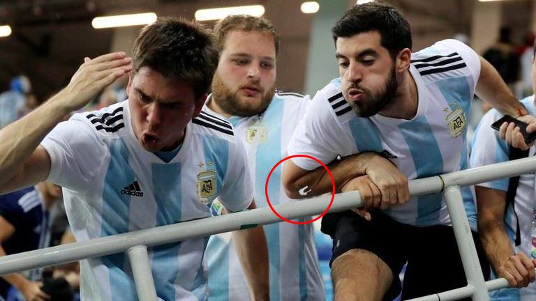 Momento en que un aficionado escupe hacia la zona de la banca argentina