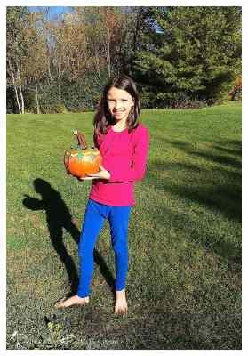 little girl holding her painted pumpkin