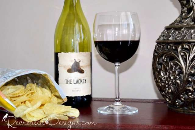 a bottle and glass of red wine and some potato chips
