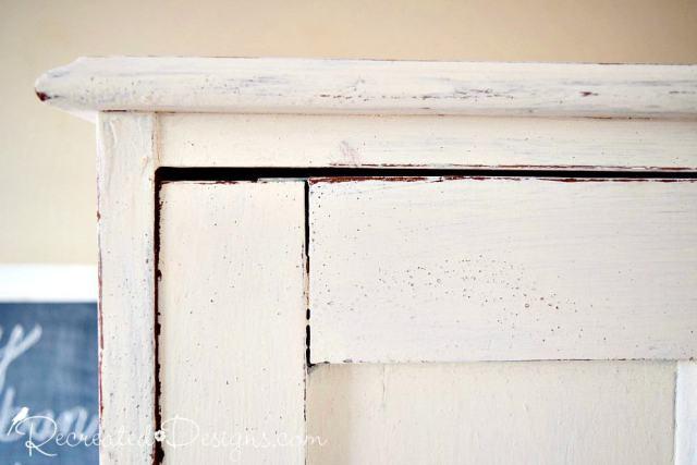 Red paint peaking through white milk paint