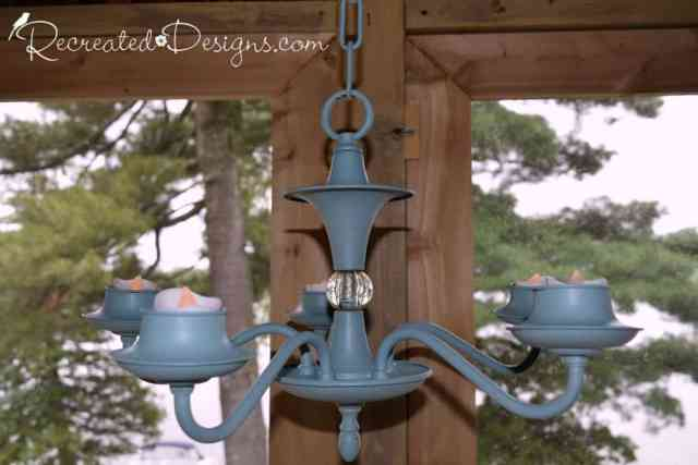 a chandelier painted with Fusion Mineral Paint with tea lights for lighting a cottage porch