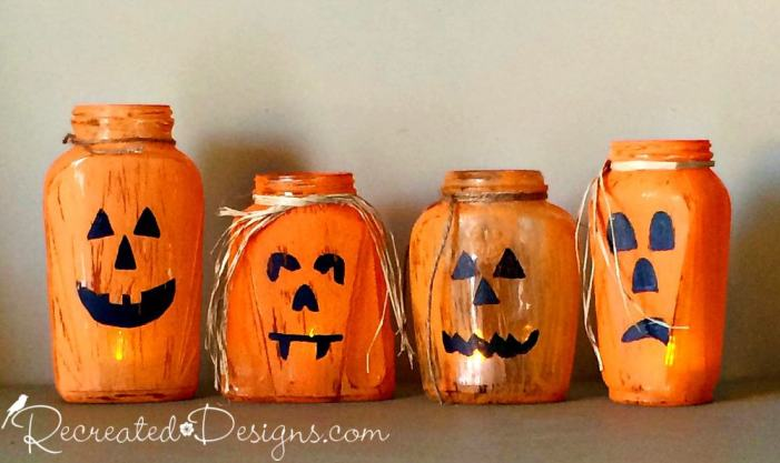 Odd shaped vintage glass jars painted like Jack-O-Lanterns with tea light inside
