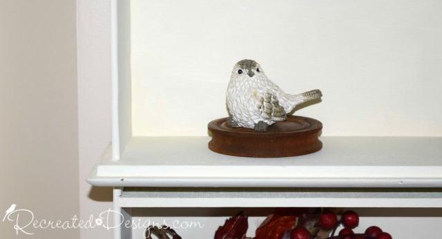 little bird sitting on a wood spool