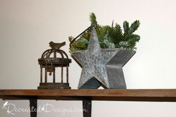 galvanized tin star with spruce sprigs and a wrought iron bird cage