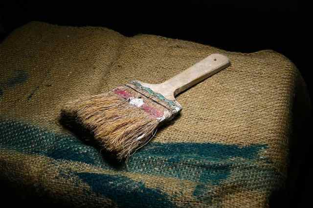 very old paint brush on burlap