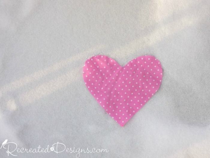 pink polka dot heart laying on snow