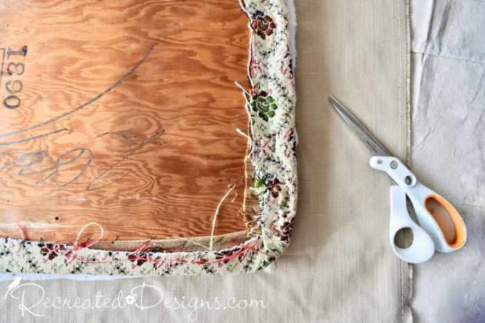 cutting a new piece of fabric to recover an old chair seat