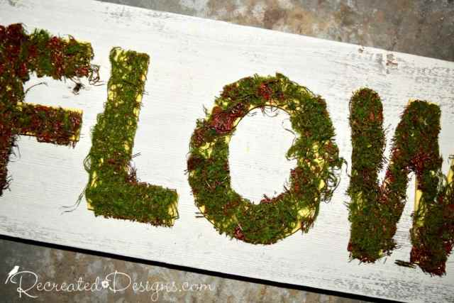 moss covered painted yellow letter on a Spring reclaimed wood sign