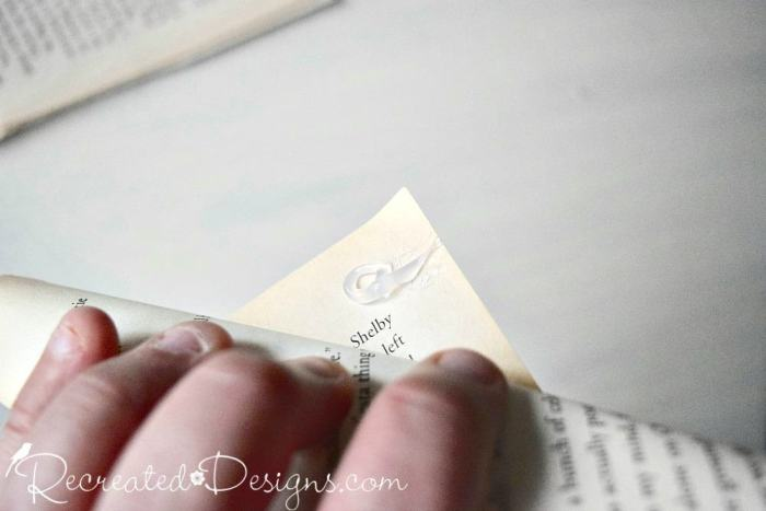 rolling old book pages and closing them with hot glue
