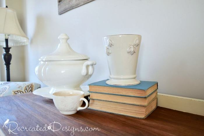 Cream Ironstone and old books sit on wood buffet top