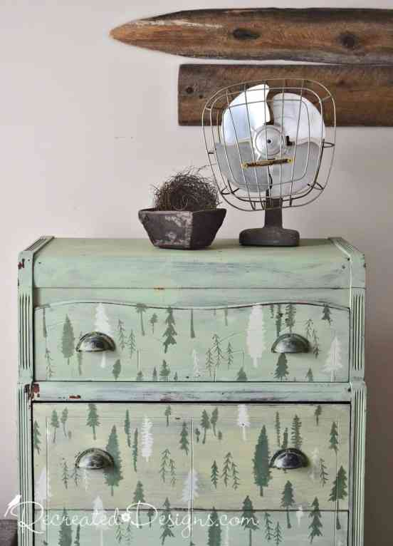 Vintage fan and antique berry box sitting on an old dresser painted green