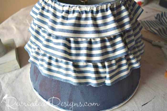 Adding ruffles to a salvaged lamp shade with vintage inspired fabric and hot glue