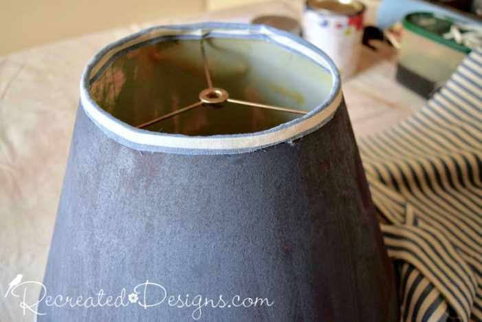 attaching a thin strip of fabric to the top of a painted lamp shade to cover the old trim