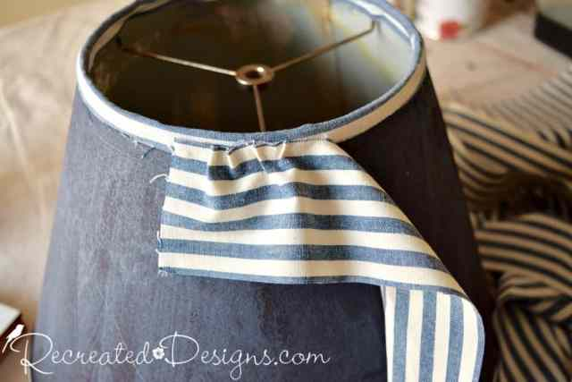 Attaching fabric to an old lamp shade by using hot glue to make ruffles