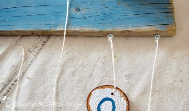 Eye hooks used for hanging wood slices from reclaimed wood
