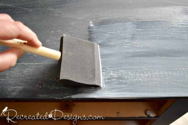 applying ModPodge before adding vintage inspired paper for furniture upcycle