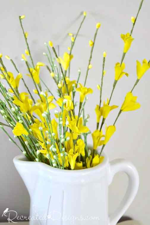 Yellow flowers in a white jug for Spring