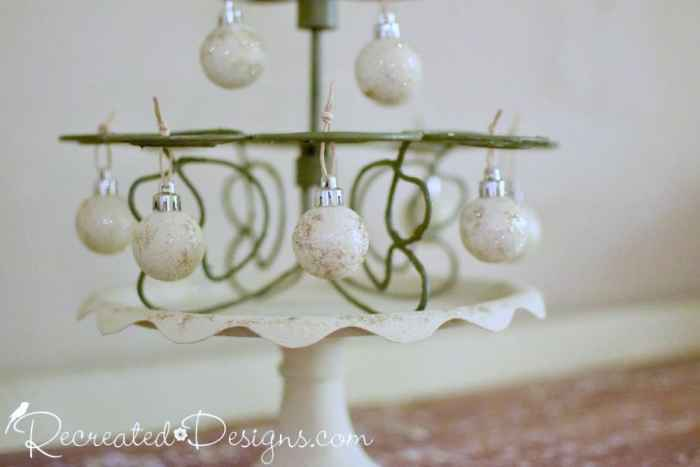 painted Christmas ornaments hanging from a cupcake holder