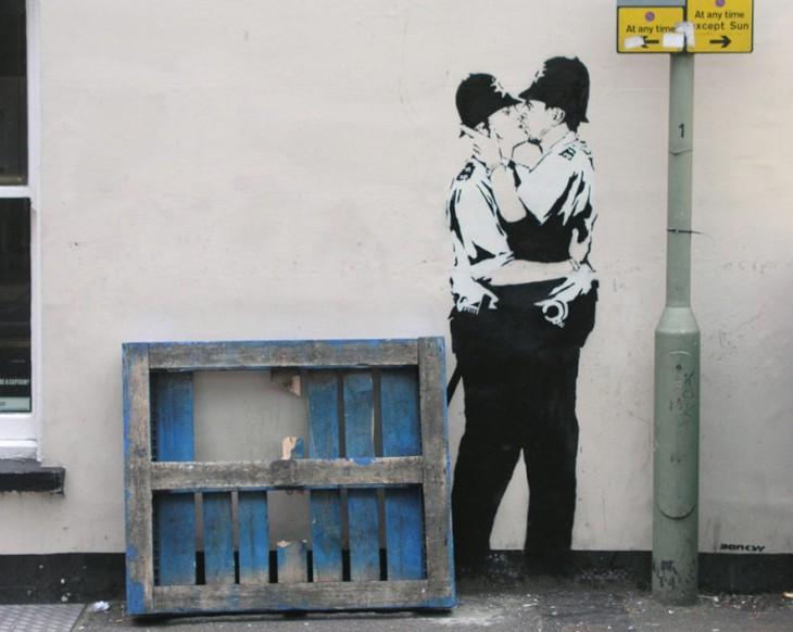 Grafiti de Bansky de dos hombres policías besándose en la boca