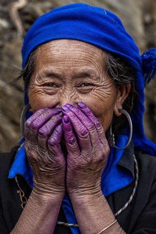 mujer con un reboso en la cabeza color azul y las manos en la boca pintadas de color purpura