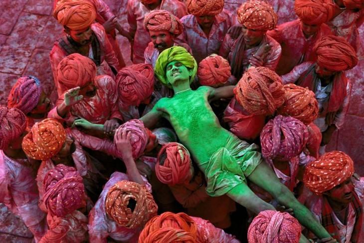 hombre sostenido por otros en los brazos mientras esta manchado de pintura verde