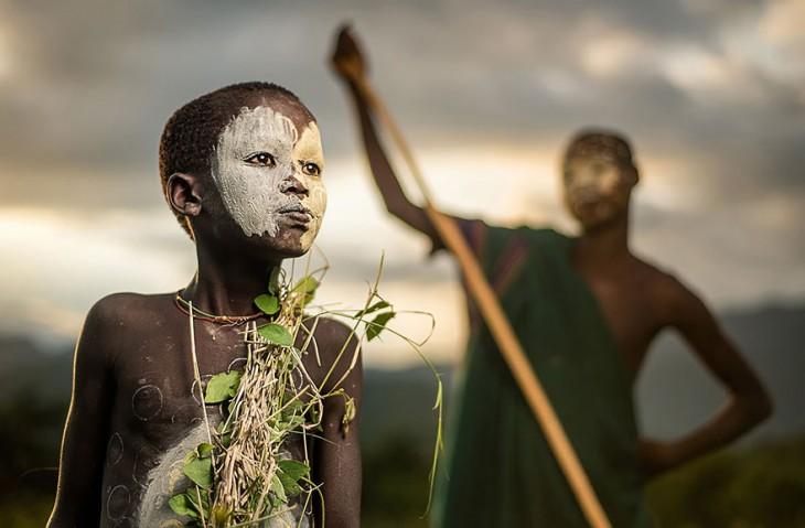 niños de una tribu africana usando vestidos verdes con ramas