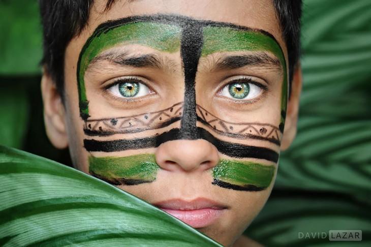 niño de ojos de color verde escondido entre las ramas