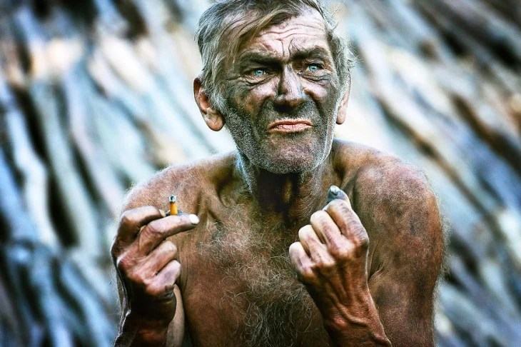 hombre lleno de carbon en el cuerpo y sosteniendo un cigarrillo en su mano