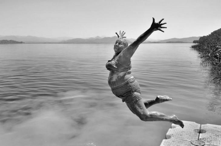 mujer saltando desde un muelle