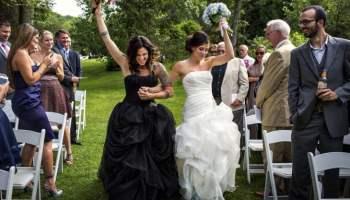 Dos chicas recién casadas caminando por el pasillo en medio de los invitados