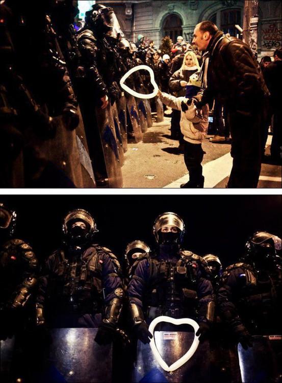 fotografía de un niño rumano que entra un globo en forma de corazón a un policía