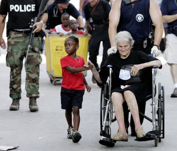 niña y una anciana víctimas de un huracán tomadas de la mano