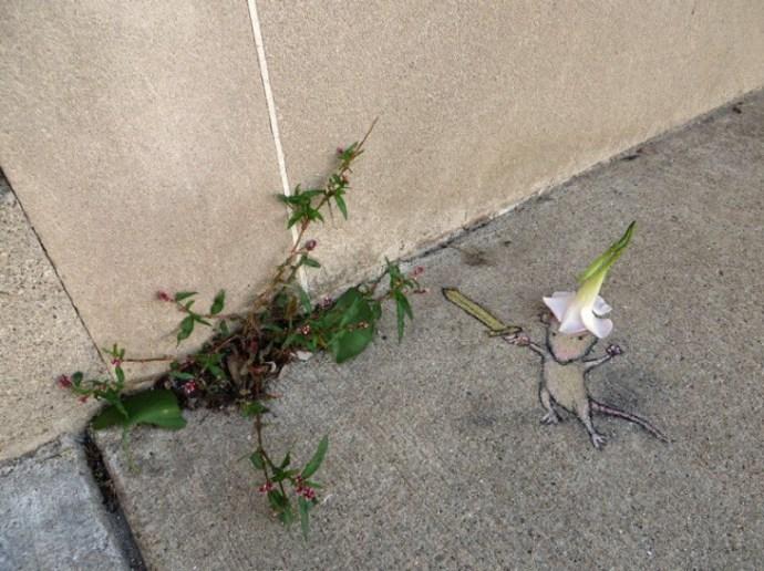 Desenho com giz de um rato interagindo com folhas saindo de cimento