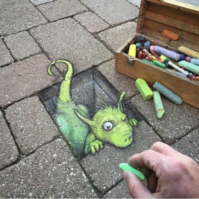 David Zinn desenho com giz em uma rua um desenho de um dragão que emerge de um banco