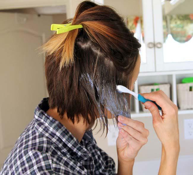 mulher que pinta o cabelo com uma escova de dentes