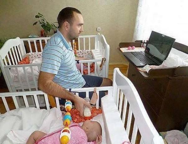 papá da biberón a sus gemelas mientras ve algo en la computadora