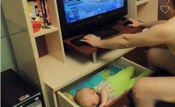 bebé dormido en un cajón mientras su papá juega en la computadora