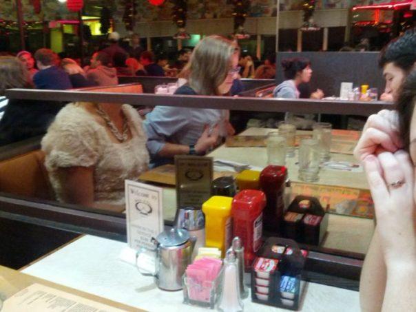 Fotografía engañosa en donde, por un espejo que divide dos mesas de un restaurante, parece que la mujer que come no tiene cabeza