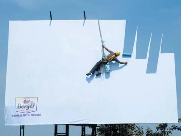 Hombre pintando un espectacular pero da la impresión que está pintando el cielo