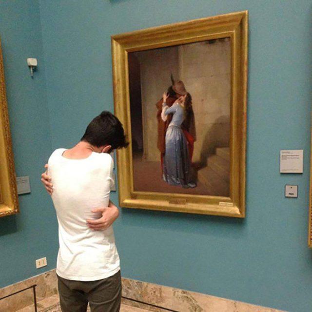 muchacho abrazándose a sí mismo frente a un cuadro de romeo y julieta