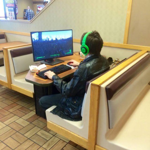chico en restorán jugando vídeojuegos