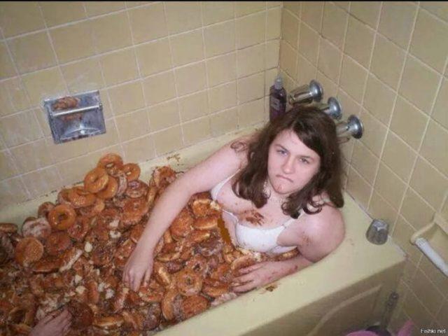 mujer en bañera llena de donas