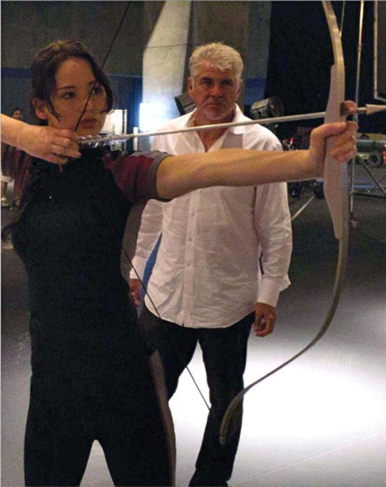 Katlyn de Los Juegos del Hambre practicando con flecha y arco