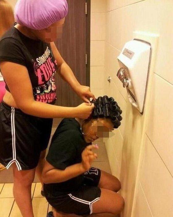 mujer secándose el cabello en el secador de manos de un baño