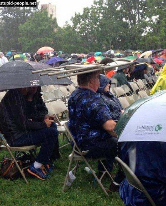 hombre usa una silla cual paraguas