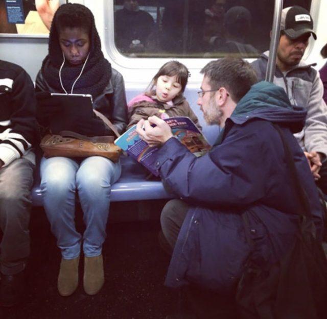 papá en el metro leyendo con su hija