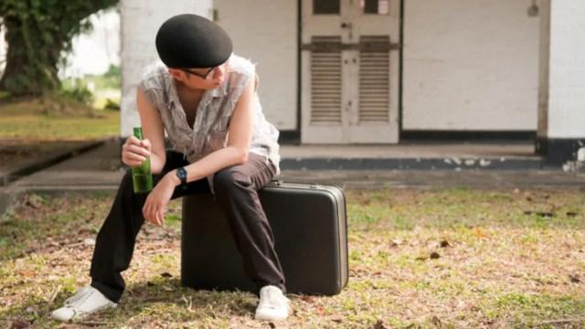 joven fuese de casa sentado en una maleta