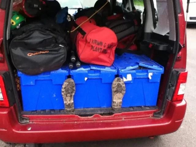 equipaje en el que sobresalen zapatos de personas