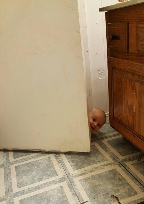 Bebé asomado en el baño