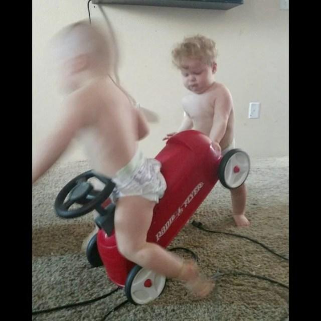niño tira del carrito a su hermanito